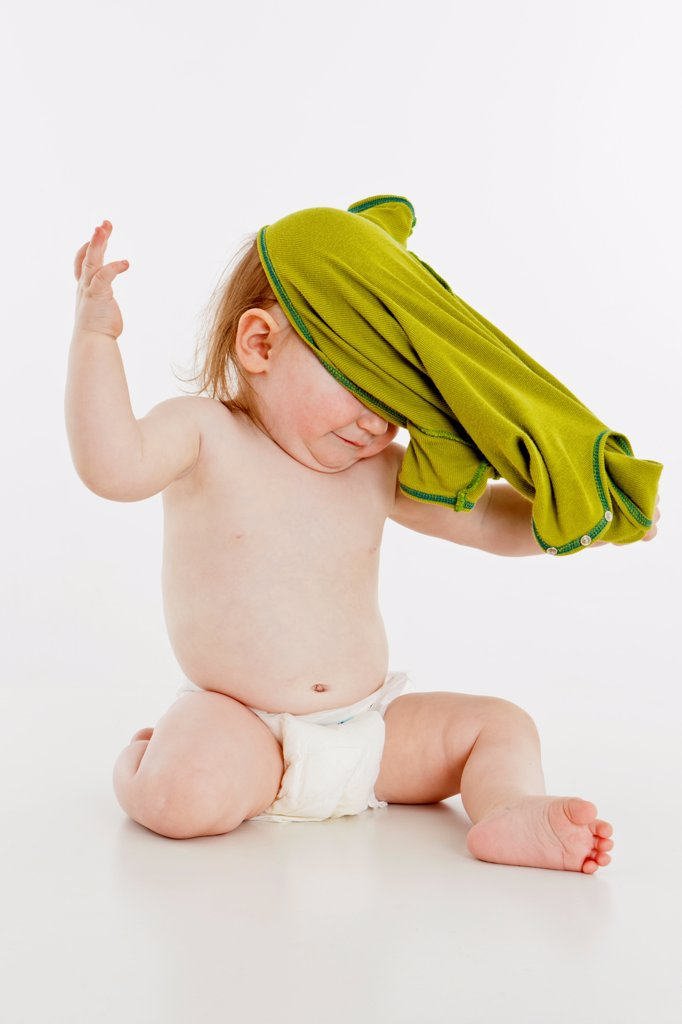 A baby girl pulling her shirt off : Stock Photo