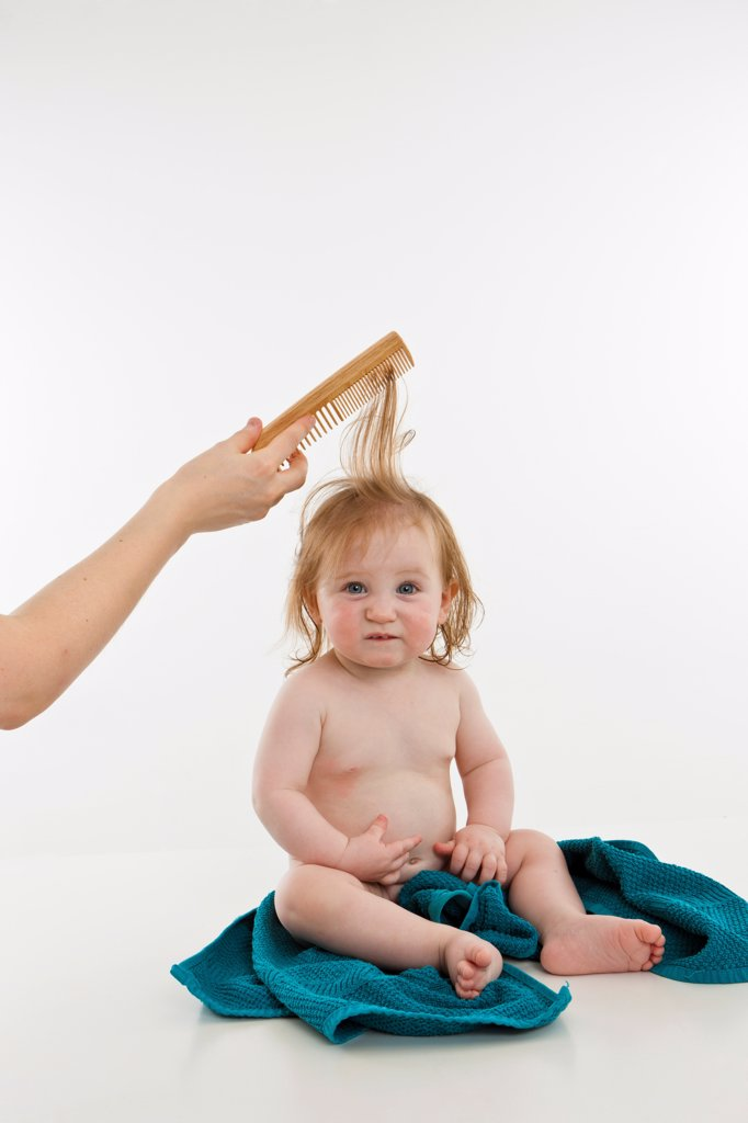 Stock Photo: 1570R-140188 A baby girl having her hair combed
