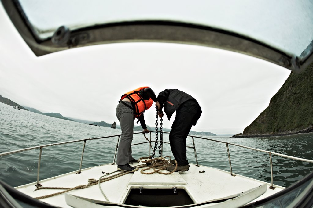 Two people engaged in lowering an anchor off the bow of a boat, Avacha Bay, Russia : Stock Photo