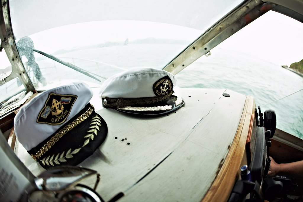 Stock Photo: 1570R-140227 Two captain's hats resting on the dashboard of a motorboat, Avacha Bay, Russia