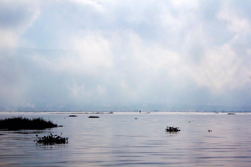 A dramatic cloudscape on Inle Lake, Burma, with a lone person on a boat in distance : Stock Photo