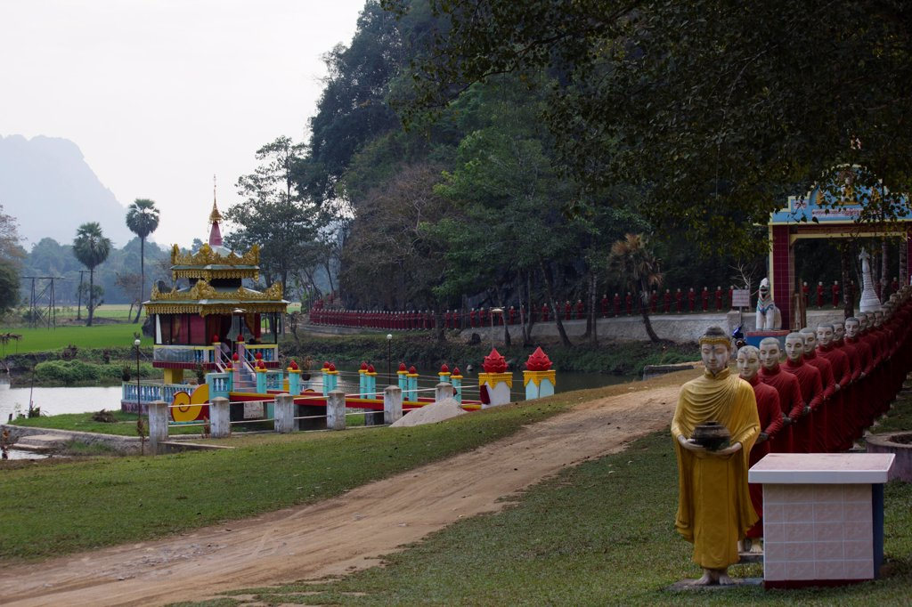 Stock Photo: 1570R-140302 A row of Buddhist monk statues in a procession behind a Buddha statue, Hpa-An, Burma