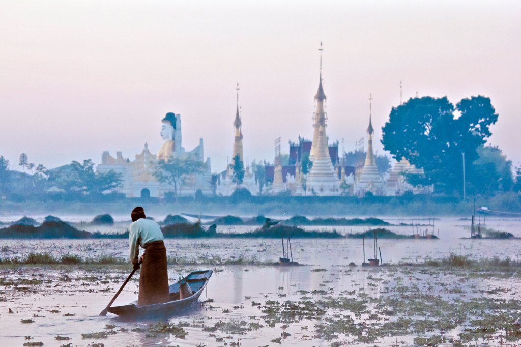 A man rowing a boat towards a temple in Burma : Stock Photo