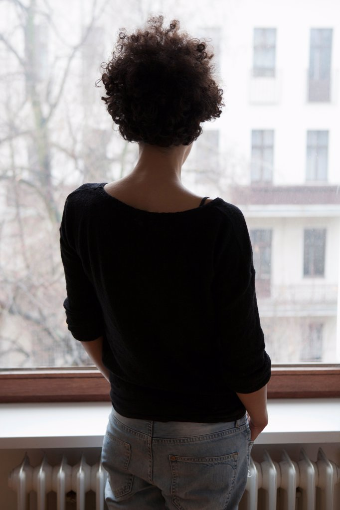 Stock Photo: 1570R-140343 Rear view of a woman looking through a window