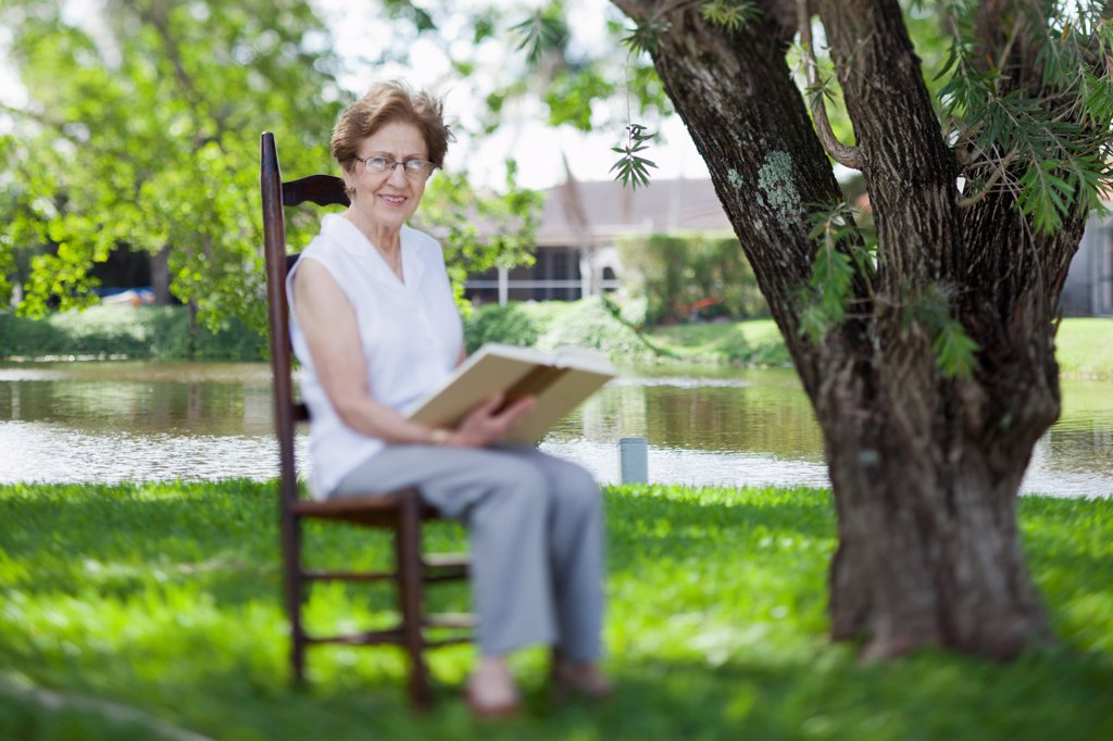 A senior woman reading next to a river : Stock Photo
