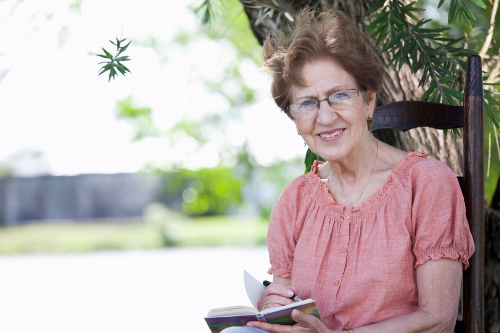 Stock Photo: 1570R-140400 Portrait of a senior woman writing in a book