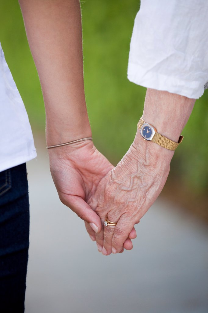 Stock Photo: 1570R-140409 Detail of a senior woman and a young woman holding hands