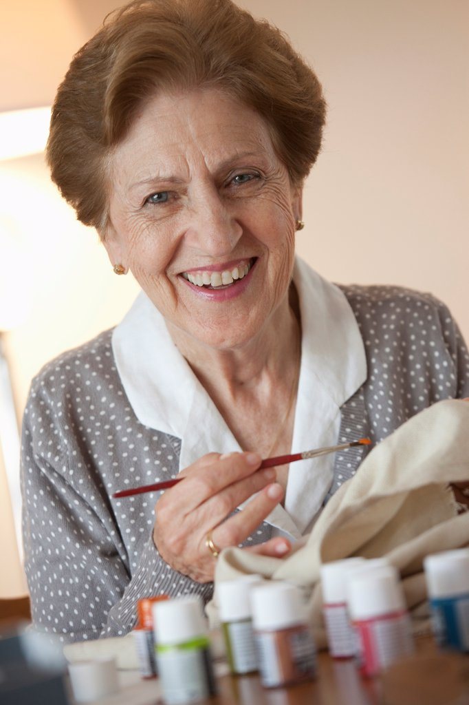 A senior woman painting on fabric : Stock Photo