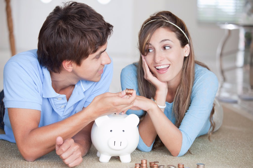 A young couple lying on the floor counting coins : Stock Photo