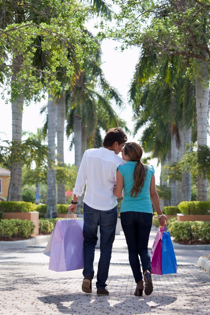 A young couple walking arm in arm and carrying shopping bags : Stock Photo