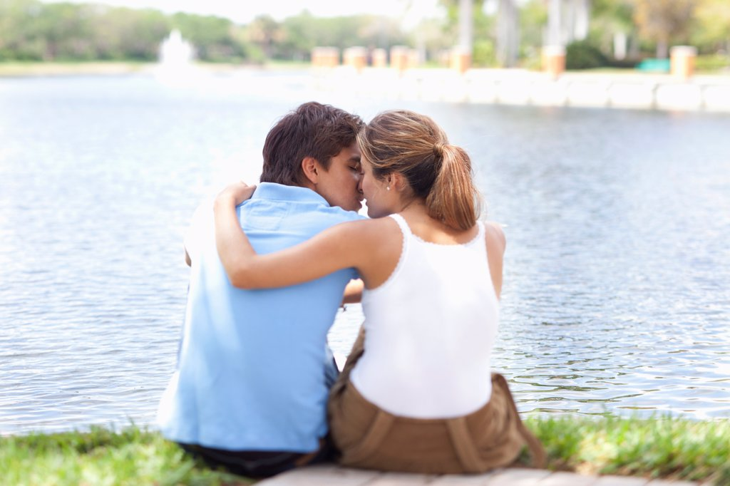 Stock Photo: 1570R-140465 An affectionate couple kissing by a lake, rear view