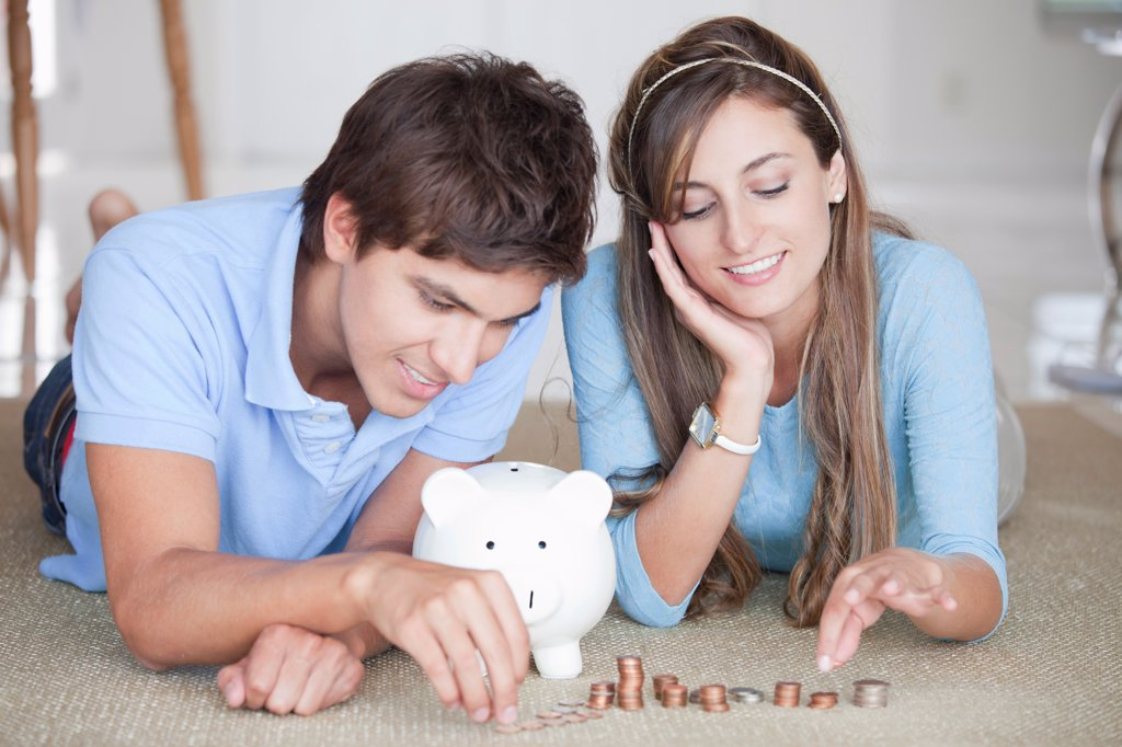 Stock Photo: 1570R-140480 A young cheerful couple counting coins on the floor