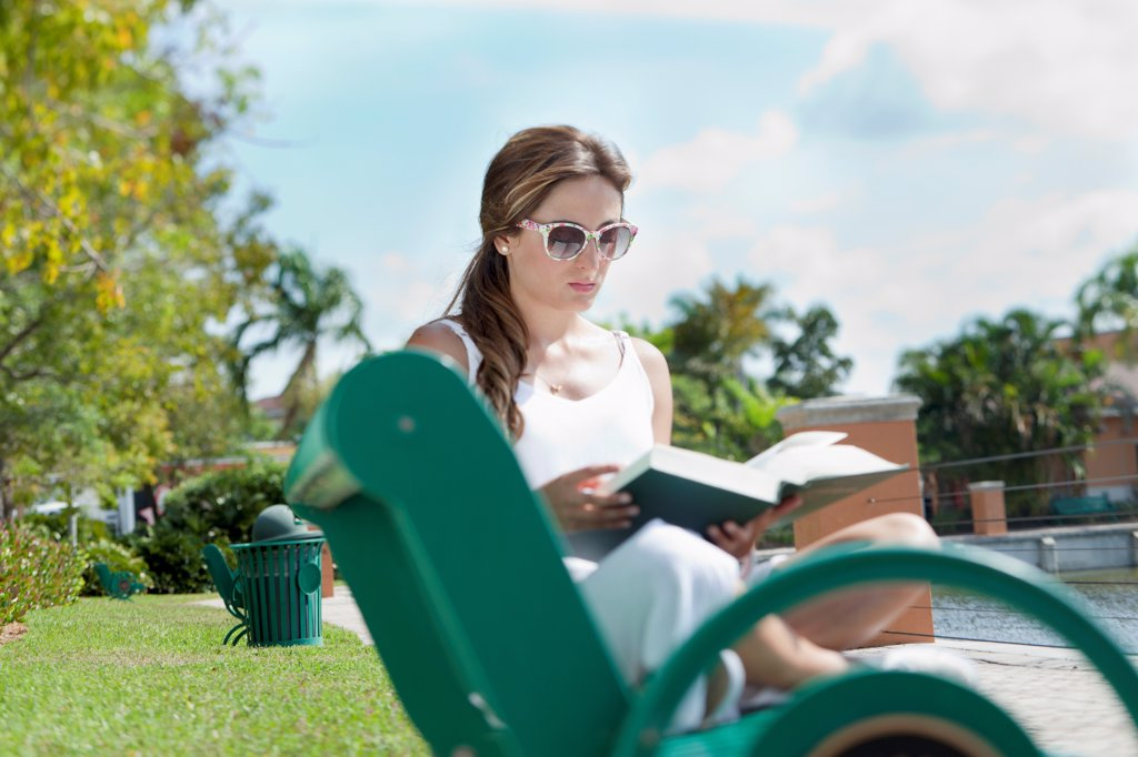 A woman reading a book on a park bench : Stock Photo