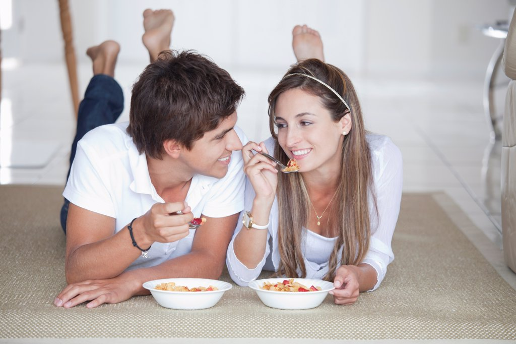A young couple flirting over their bowels of cereal : Stock Photo