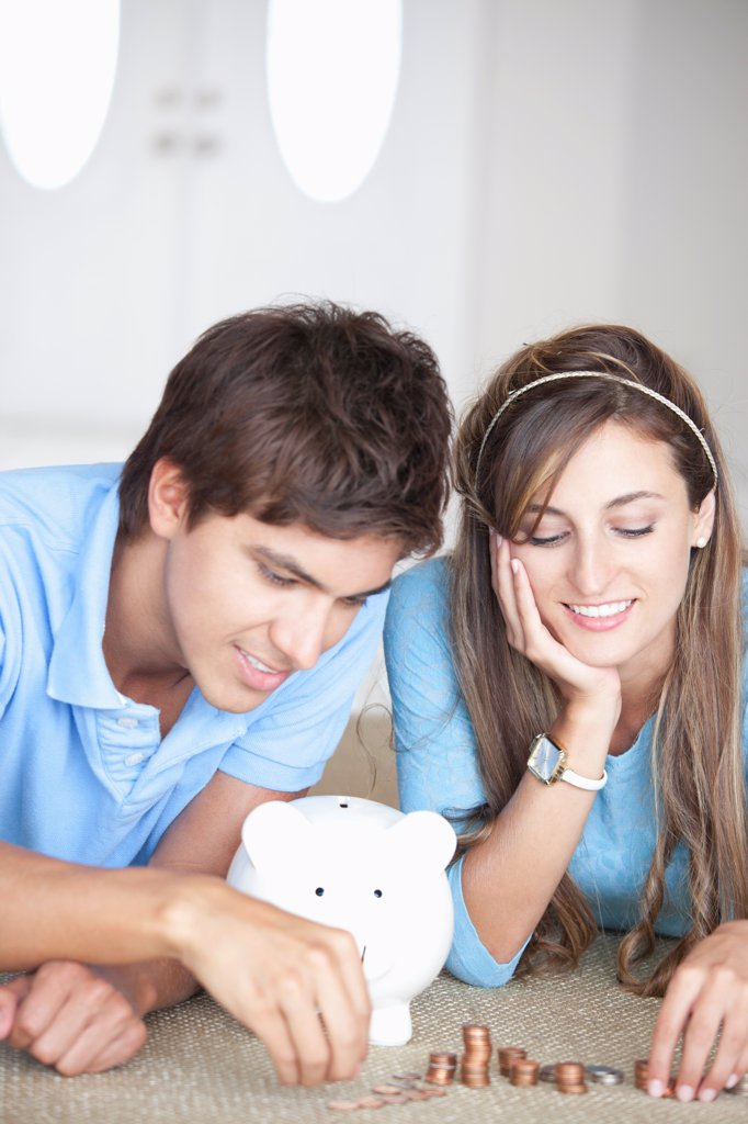 Stock Photo: 1570R-140505 A young cheerful couple counting coins on the floor