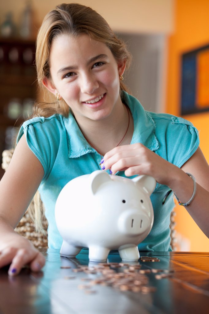 Girl puts coin in piggy bank : Stock Photo