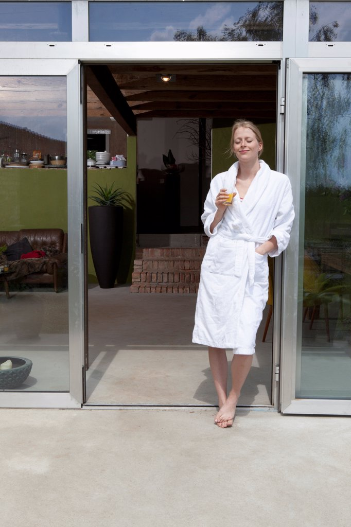 A woman standing in the doorway of her house in a bathrobe enjoying the morning : Stock Photo