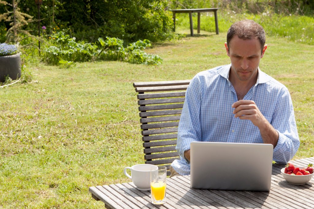 Stock Photo: 1570R-140543 A man sitting at a table in his backyard having breakfast and using a laptop
