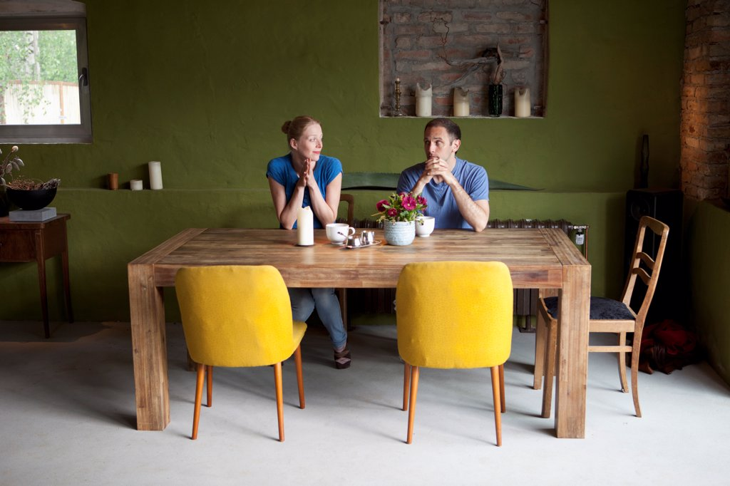 Stock Photo: 1570R-140552 A couple sitting at a dining table looking at each other uncertainly