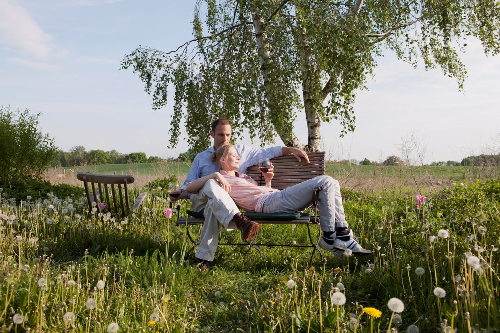 A couple enjoying sunshine and wine on a bench in their backyard : Stock Photo