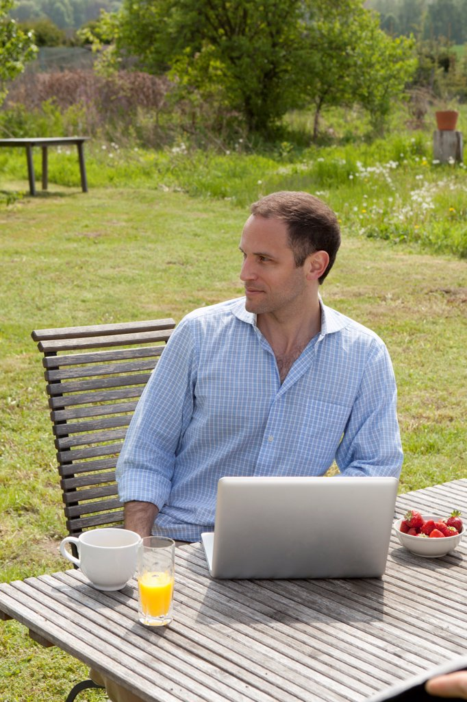 Stock Photo: 1570R-140562 A man sitting at a table in his backyard having breakfast and using a laptop