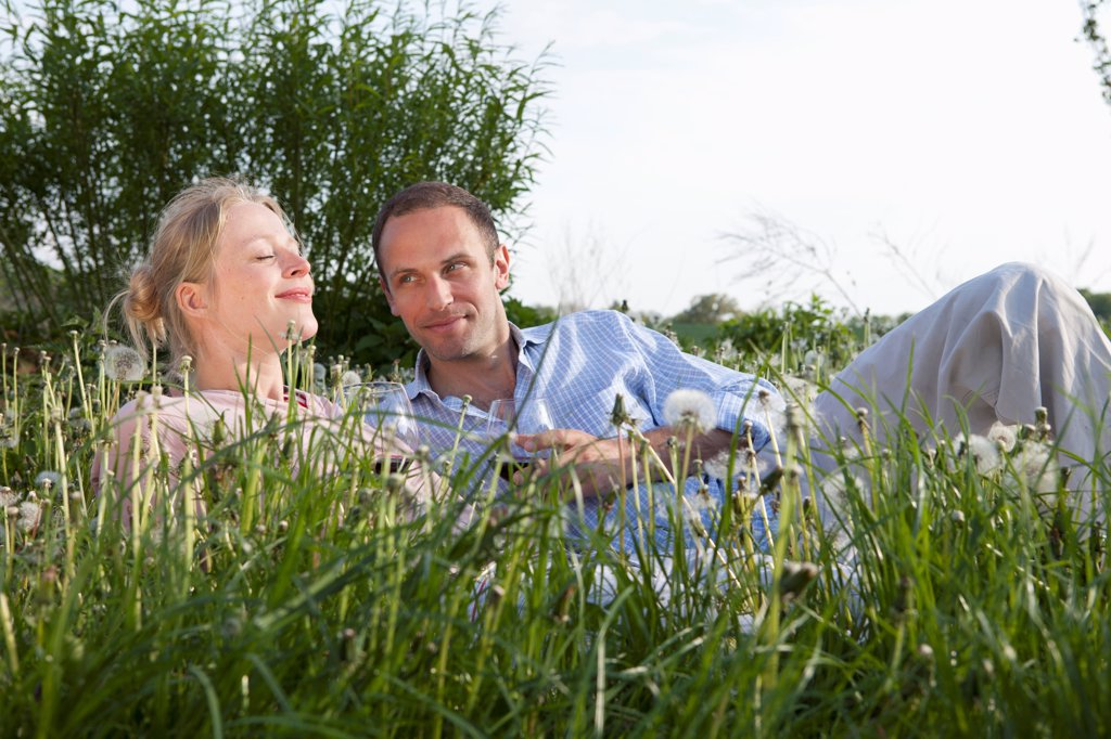 Stock Photo: 1570R-140577 A couple lying in the grass enjoying some red wine