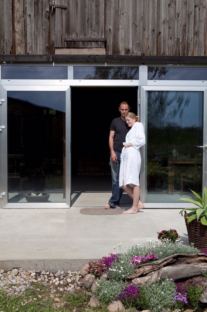 Stock Photo: 1570R-140589 A couple leaning against the doorway of their house in the morning
