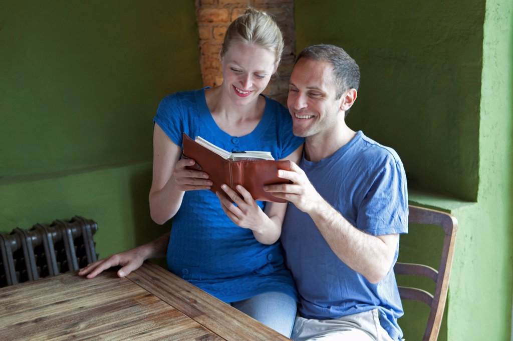 Stock Photo: 1570R-140590 A couple reading a personal organizer together and smiling