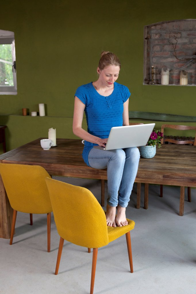 A woman sitting on her dining table using a laptop : Stock Photo