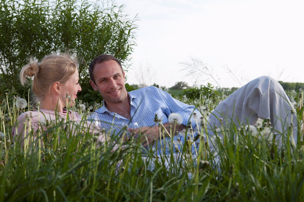 Stock Photo: 1570R-140603 A couple lying in the grass enjoying some red wine