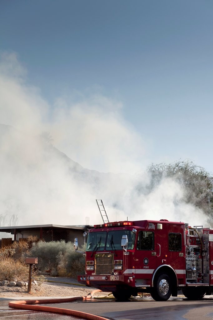 Stock Photo: 1570R-140628 A fire truck next to a burning house in a suburb