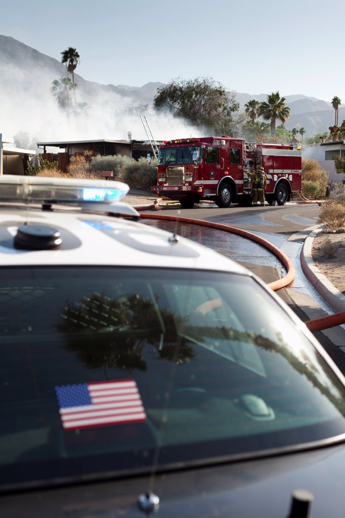 Stock Photo: 1570R-140630 A police car and a fire truck at the scene of a burning house in a suburb