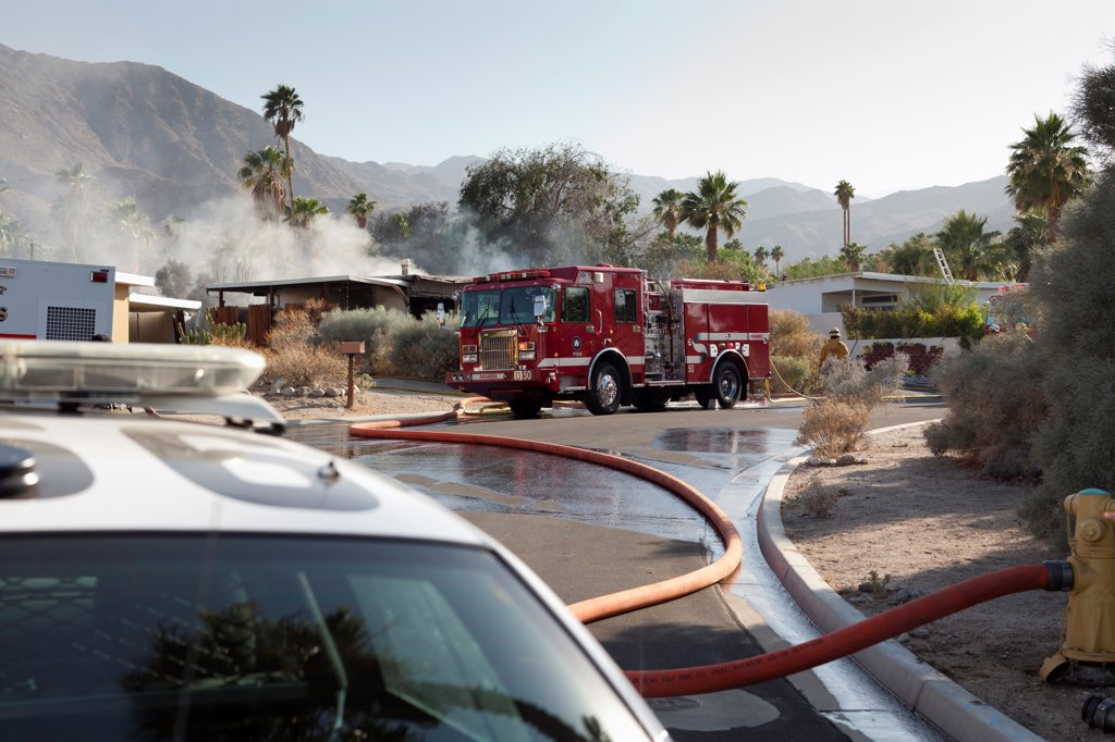 Stock Photo: 1570R-140639 A police car and a fire truck at the scene of a burning house in a suburb