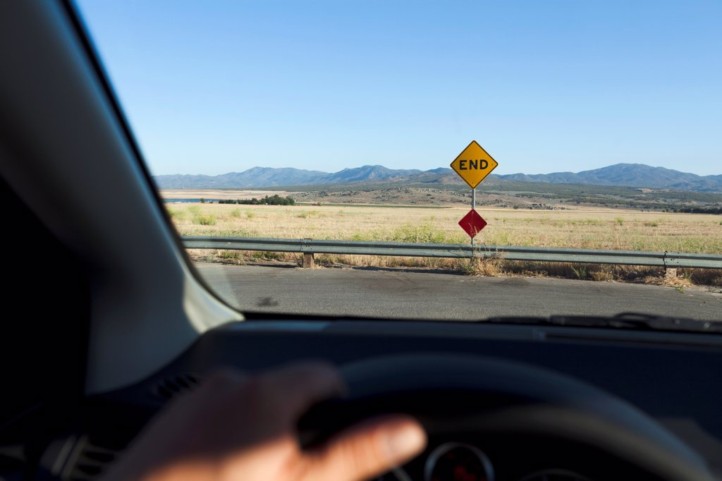 Stock Photo: 1570R-140656 View through a car windshield of an END road sign and mountain ranges behind