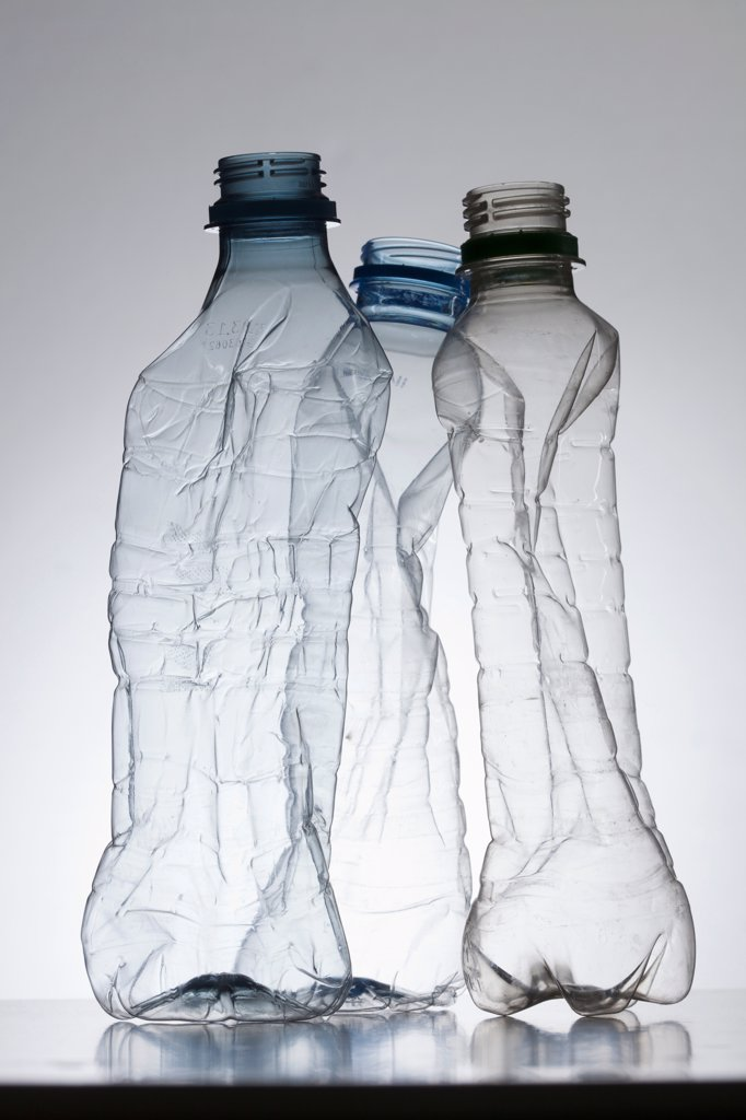Three empty, partially crushed plastic water bottles : Stock Photo