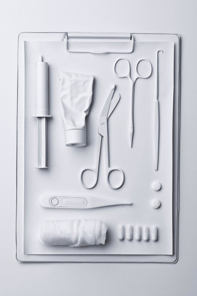 Medicine and medical equipment painted white and laid out on a clipboard : Stock Photo