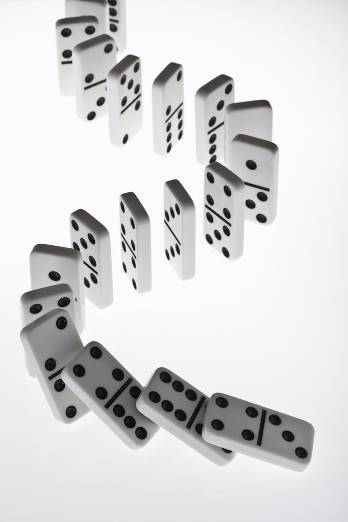 Stock Photo: 1570R-140735 Dominoes in a row, beginning to fall over in a chain reaction