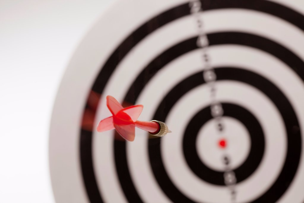 Stock Photo: 1570R-140737 Rear view of a dart flying towards the bull's eye of a target