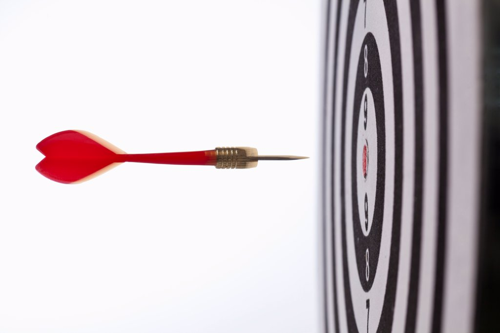 Side view of a dart flying towards the bull's eye of a target : Stock Photo