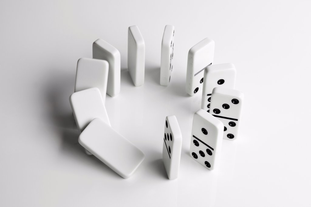 Dominoes in a circle beginning to fall over in a chain reaction : Stock Photo