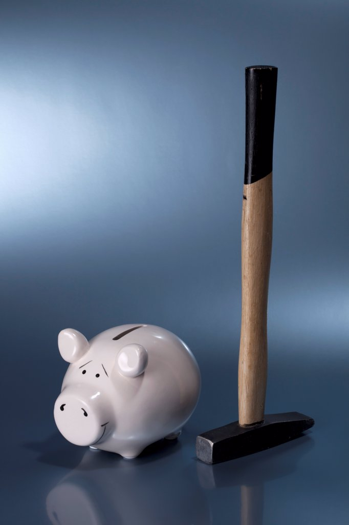 Stock Photo: 1570R-140826 A sledgehammer next to a ceramic piggy bank