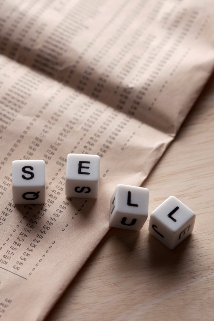 Lettered cubes spelling SELL lying on top of a financial page : Stock Photo