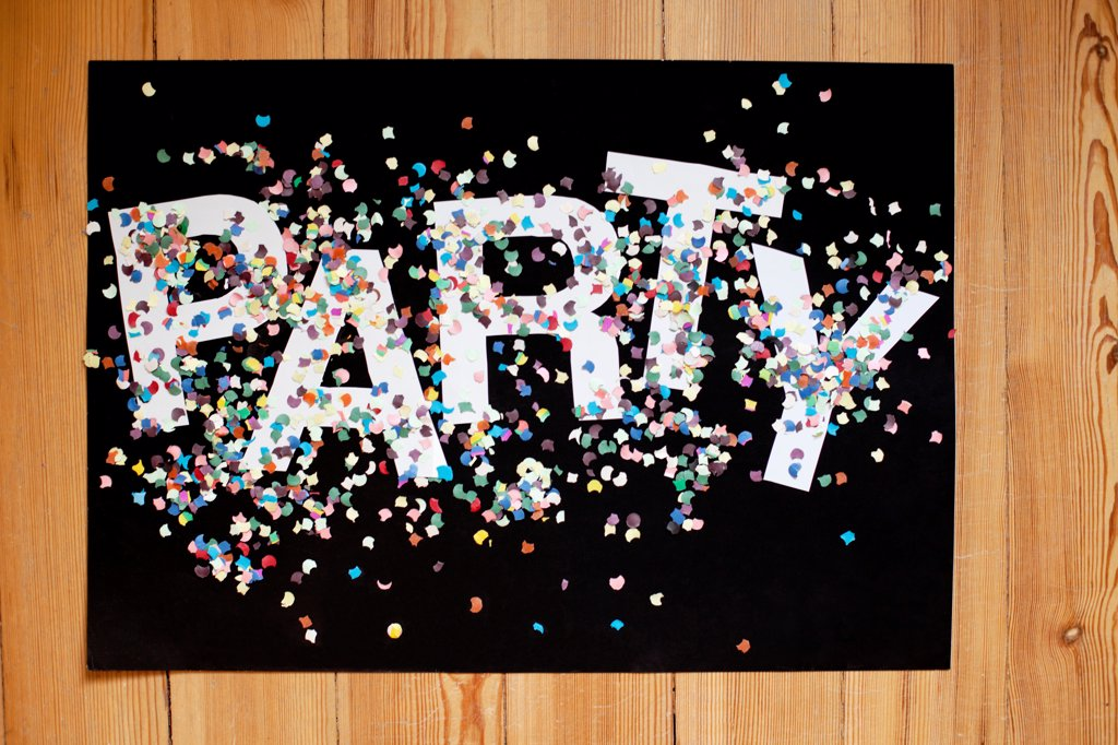 Stock Photo: 1570R-140865 Confetti and letters spelling PARTY on a black poster board