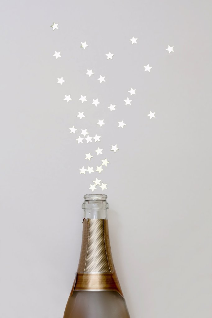 Stock Photo: 1570R-140877 Star shaped confetti spraying out of a champagne bottle