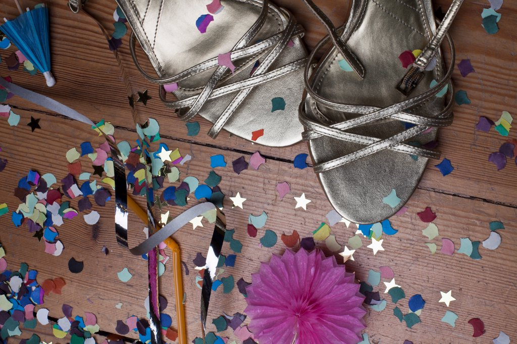 Metallic strappy heels, confetti and streamers littering a hardwood floor : Stock Photo