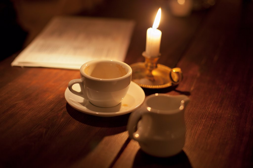 Empty cup of coffee by the candle light : Stock Photo