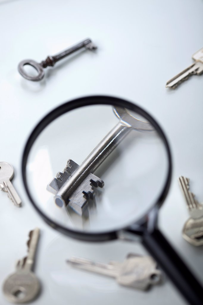 A key lying amongst many being magnified by a magnifying glass : Stock Photo