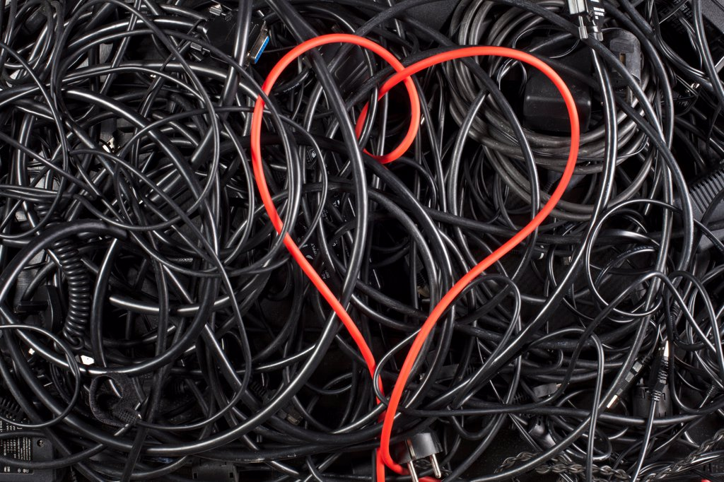 Stock Photo: 1570R-140975 A red cord in a heart shape amongst tangled black cables and cords