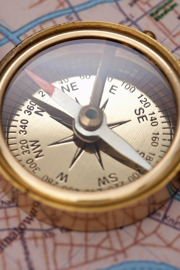 A compass on top of a road map, focus on compass : Stock Photo