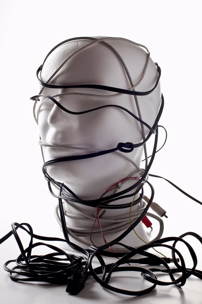 A white mannequin bust entangled in various cords and cables : Stock Photo